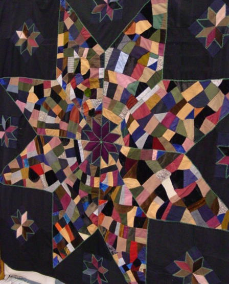 view of quilt shown hung on a rack