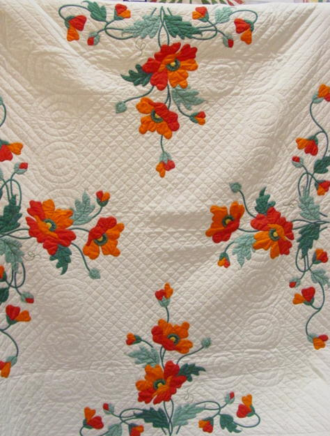 view of Poppies Applique quilt- showing most except scaolloped outer border and red binding