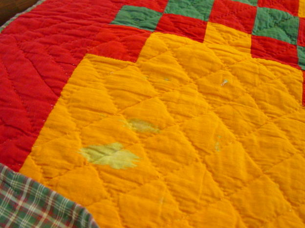 the spots of color loss- shows colors and quilting and a bit of the plaid backing
