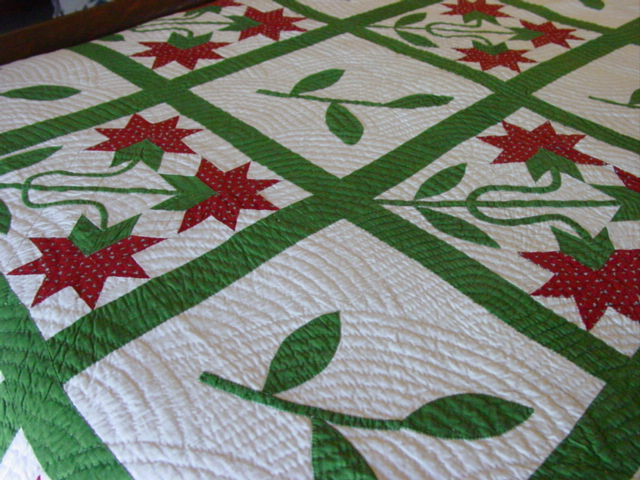 another displayed on a bed- look at the amount of quilting
