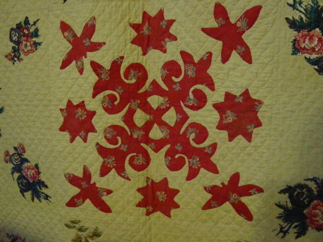 this red fleur de leis is the central block of the quilt