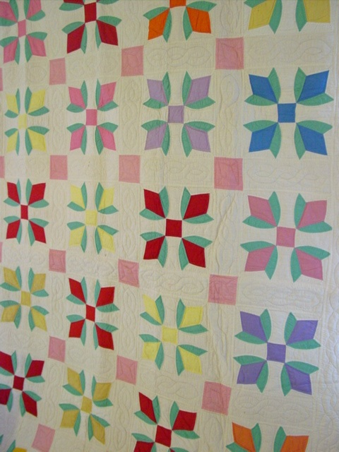 view of dated 1940 Tulip quilt hanging on a wall