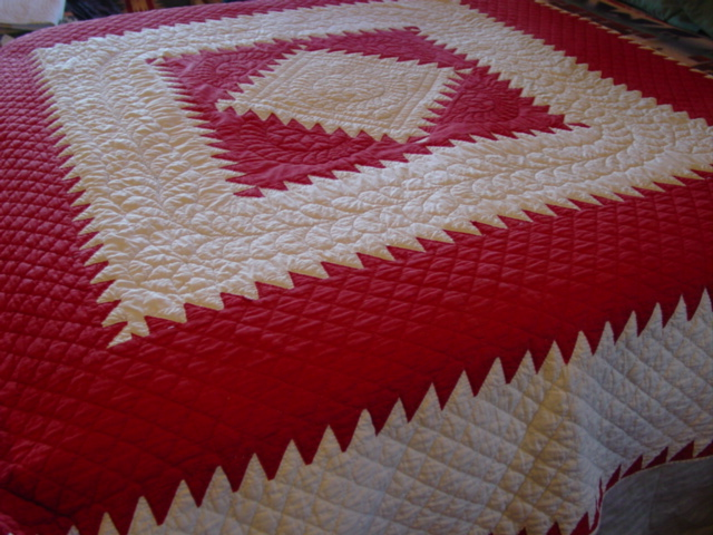 Red and White Sawtooth Square in a Square antique quilt- shown on a bed